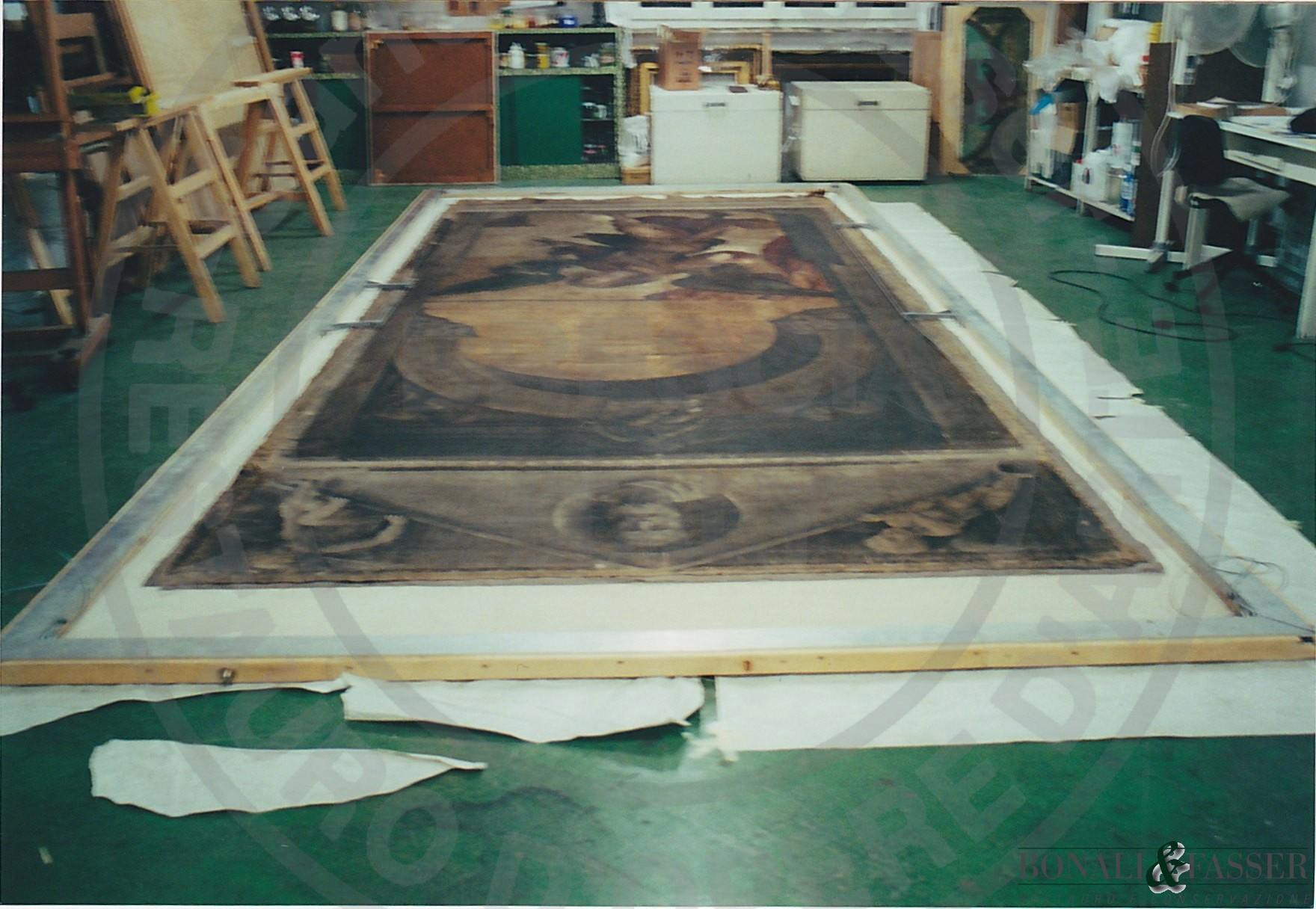 Fase di lavorazione: il dipinto tensionato su telaio interinale durante la fase di foderatura